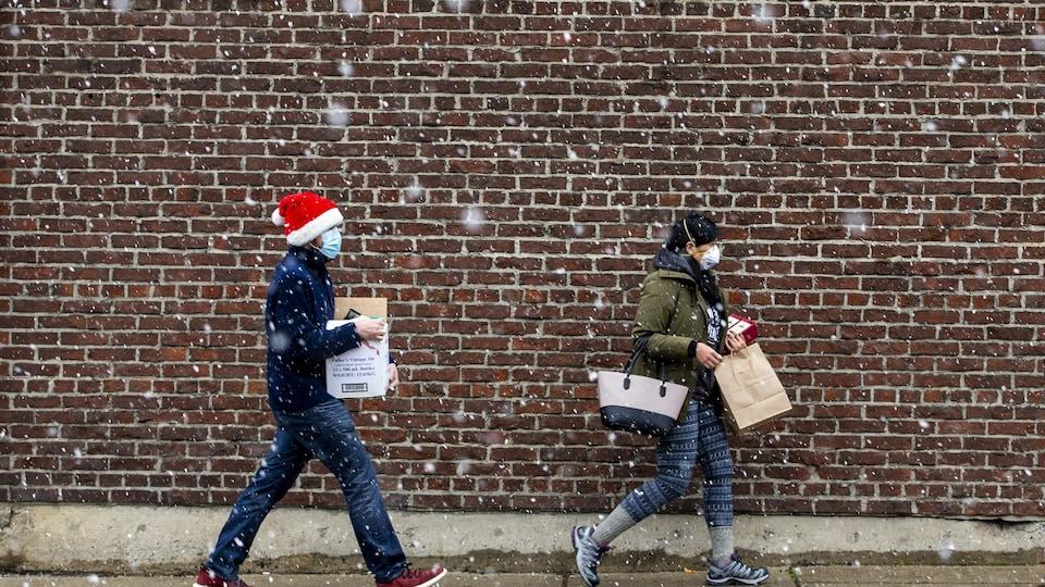 Deux personnes marchent sous la neige avec des sacs de magasinage à Toronto le 22 novembre 2020. L'une d'elles est coiffée d'une tuque de Noël.
