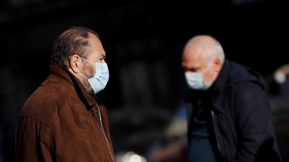 Deux hommes d'un certain âge, le visage couvert d'un masque, se croisent dans une rue à Rome, en Italie, le 18 décembre 2020.