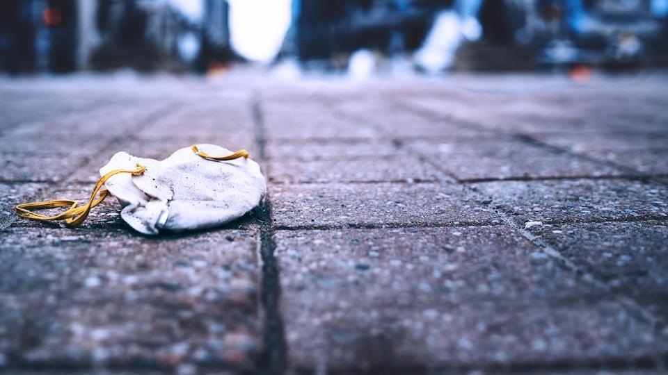 Un masque N95 laissé au sol sur la rue Sparks, au centre-ville d'Ottawa le 18 mars 2020.