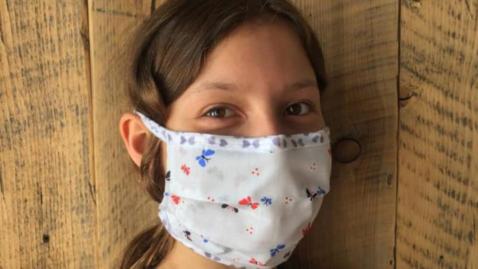 Une jeune fille porte un masque en tissu.