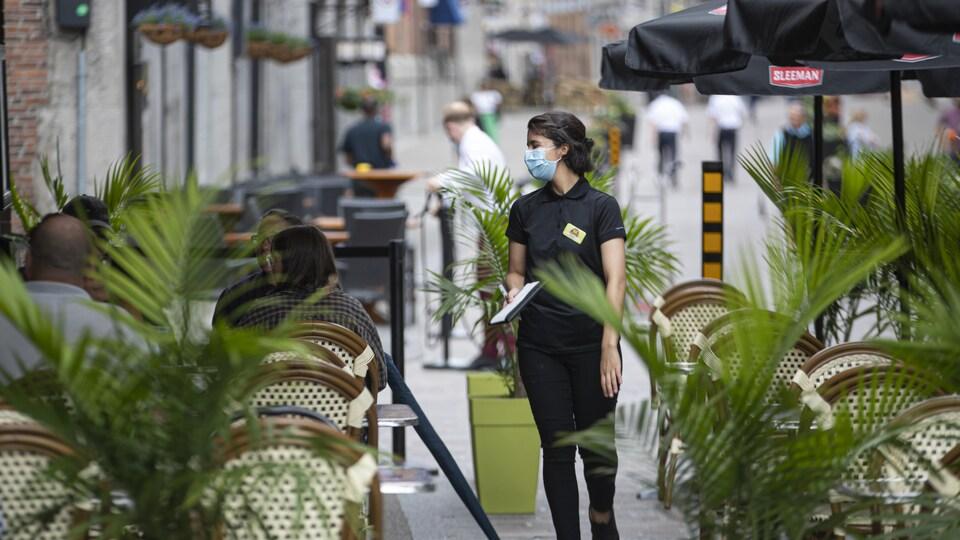 Quelques clients assis sur une terrasse d'un restaurant du Vieux-Montréal.