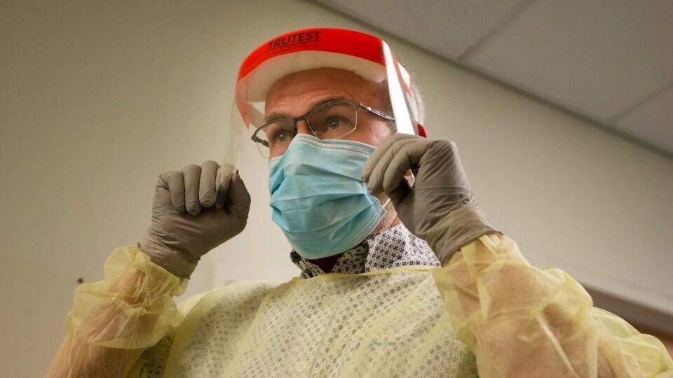 Un médecin porte l'équipement de protection individuelle : un masque, une blouse, des gants et une visière.