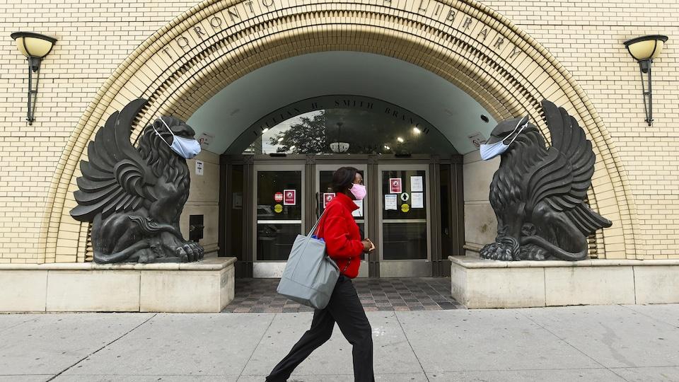 Une femme portant un masque passe devant une bibliothèque où deux statues d'aigles ont aussi un couvre-visage.