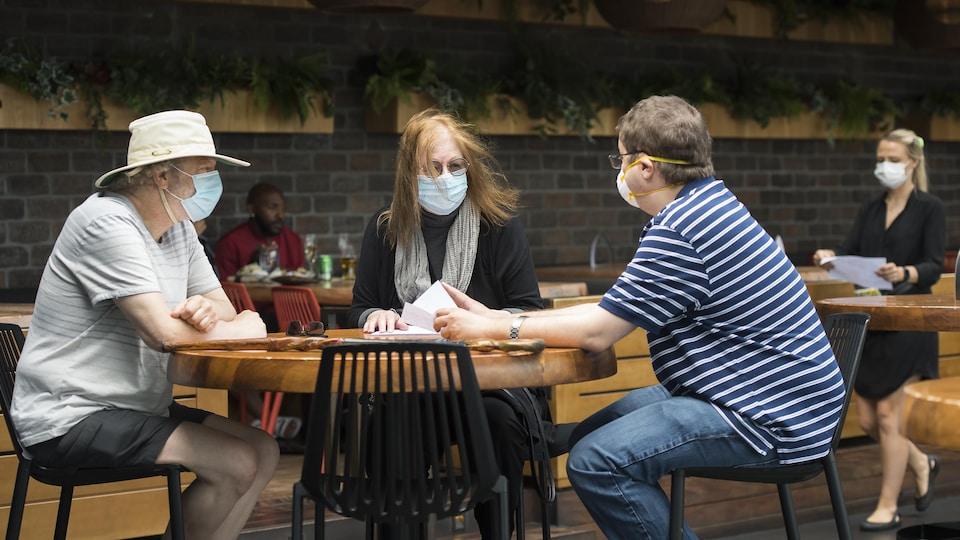Trois clients portant un masque sont assis à une table.