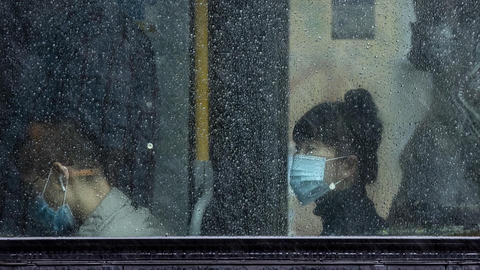 Des gens, que l'on aperçoit à travers une fenêtre embuée par la pluie, portent un masque dans un autobus de Vancouver.