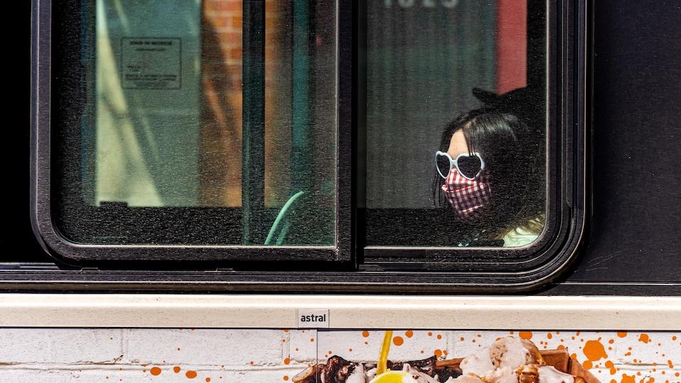 Une femme portant un masque est assise dans un bus à Montréal.