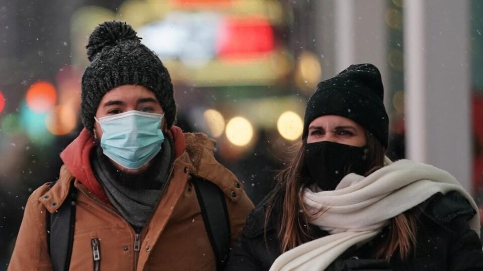 Des femmes portant des masques marchent dans la rue en hiver avec des sacs, le 16 décembre 2020 à New York.