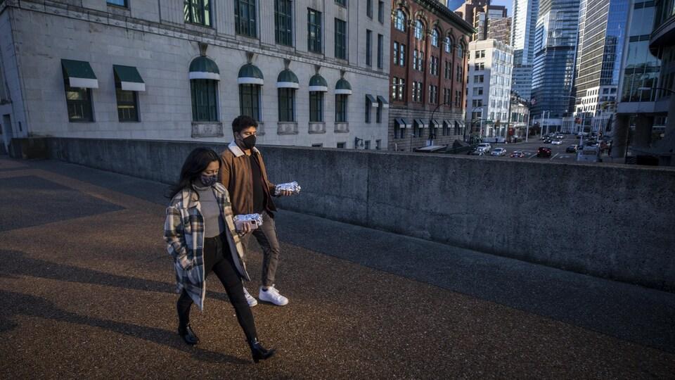 Deux personnes portant un masque marchent au centre-ville de Vancouver.