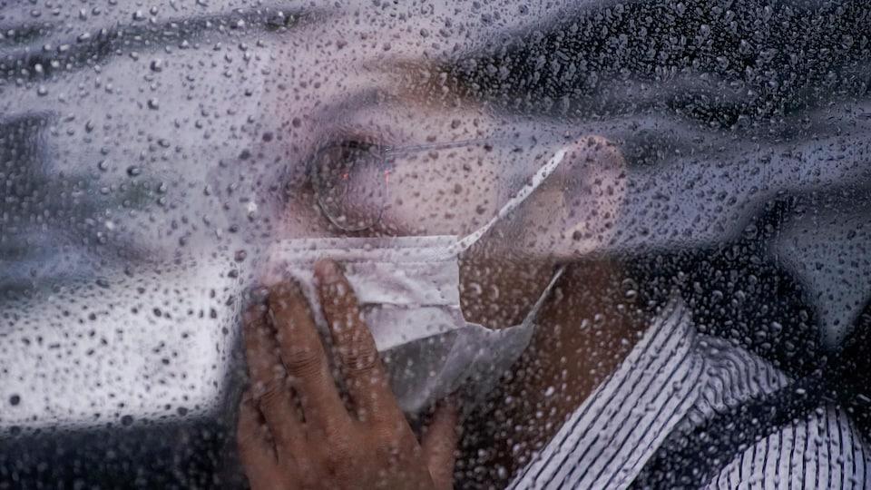 Un homme portant un masque est assis dans une voiture. La fenêtre est couverte de gouttes de pluie.