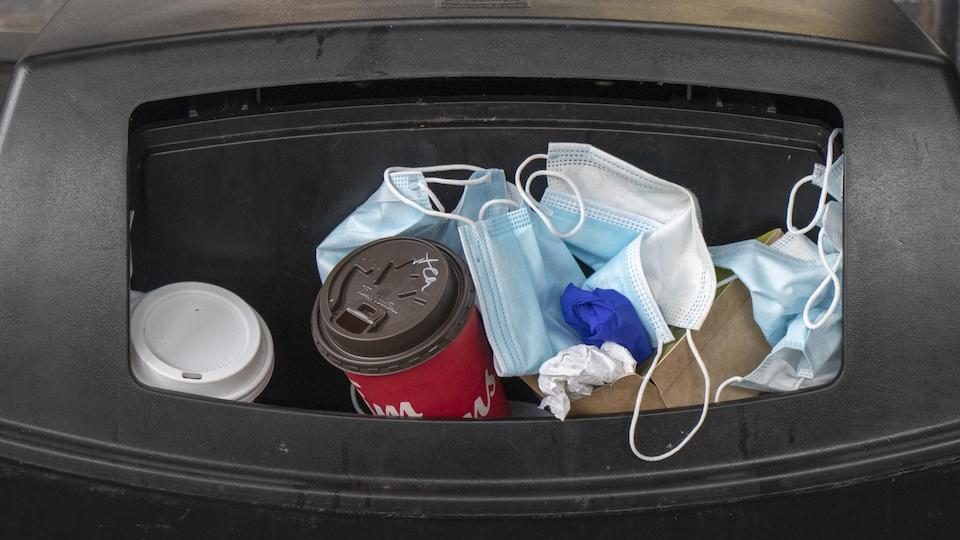 Des masques, gants et des gobelets de café débordent d'une poubelle.