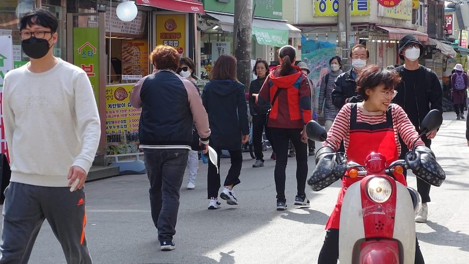 Des gens déambulent dans une rue commerciale.