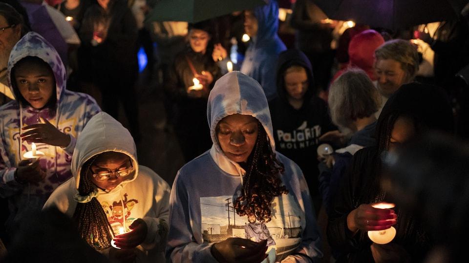 La gente se reúne y sostiene velas.
