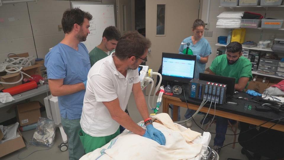 On voit une équipe qui effectue un massage cardiaque sur un corps. Des tubes et des appareils servent à prendre des mesures.