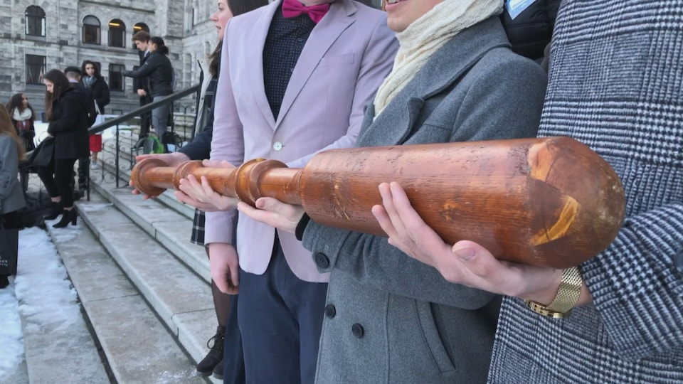 Des mains soutiennent la masse de bois.