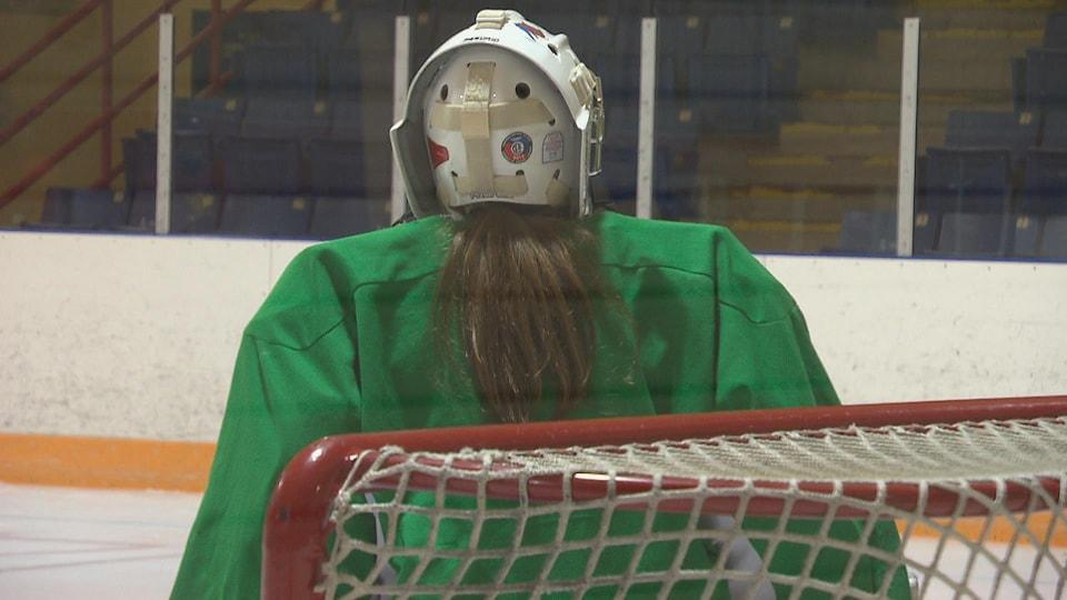 La seule chose qui la distingue Annick Boudreau des garçons sur la glace, c'est la couette qui dépasse derrière son masque.