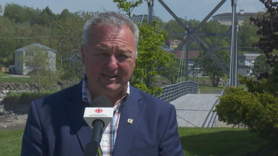 Le maire de Matane s'adresse aux médias lors d'une journée ensoleillée.