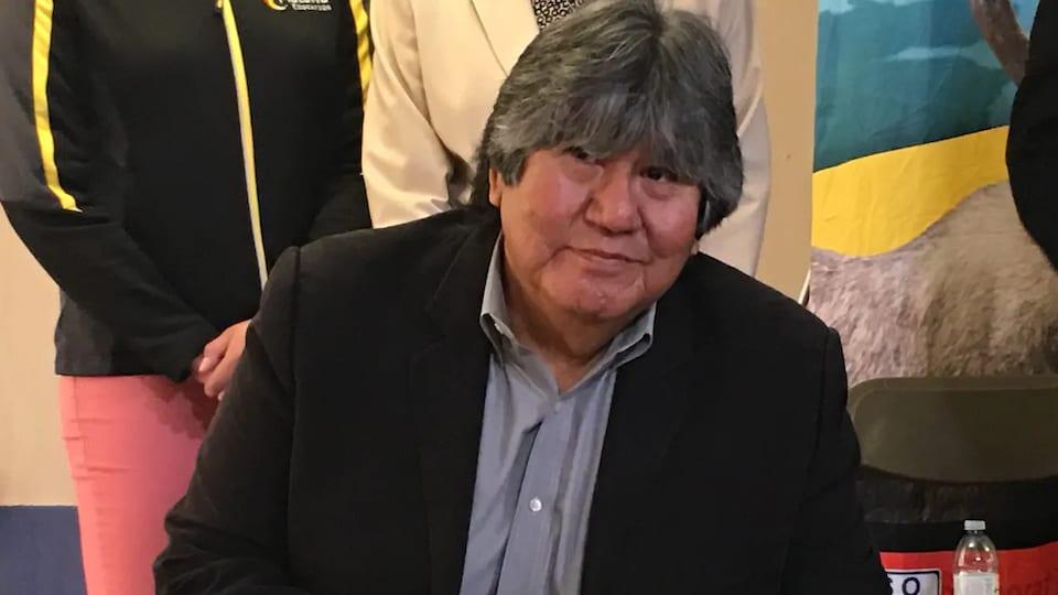 David Paul Achneepineskum en train de signer un document.