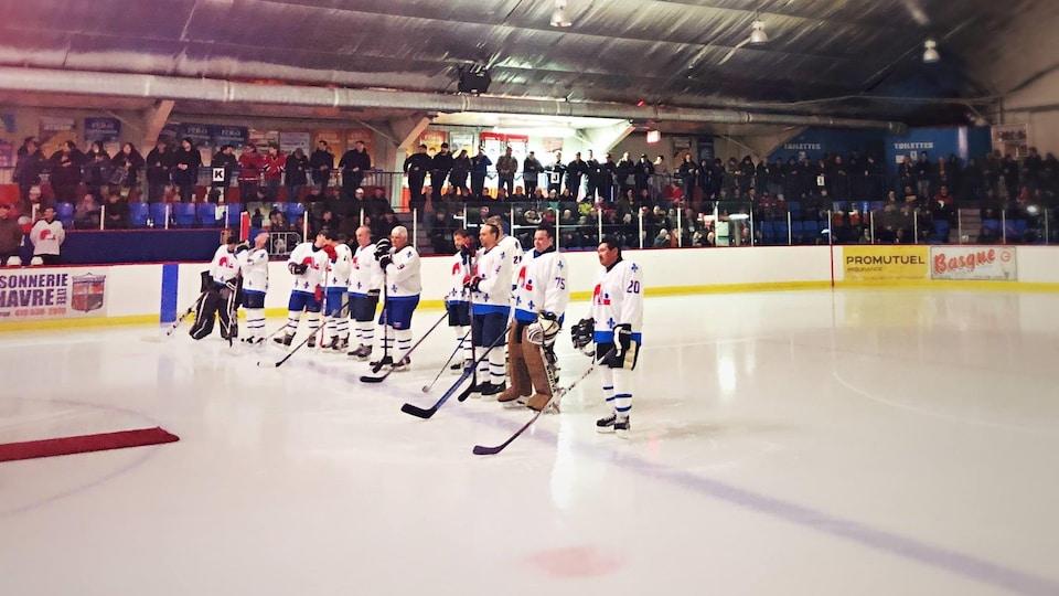 Des joueurs arborant des chandails des Nordiques de Québec sont alignés derrière la ligne bleue de la patinoire.