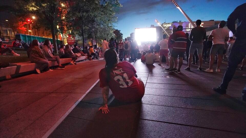 Un homme portant un t-shirt de Carey Price, assis à la Place des festivals.