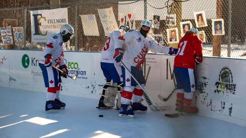 Quatre joueurs de hockey sont l'un à côté de l'autre pour récupérer une rondelle.