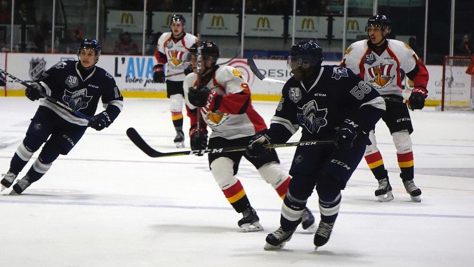 Des joueurs de l'Océanic et du Drakkar sur la patinoire. À l'avant-plan, on distingue le défenseur Christopher Inniss.
