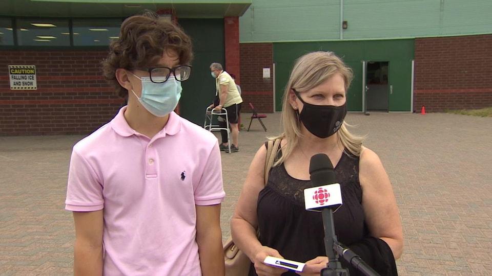 Mateo et Lynn portent un masque et sont devant la clinique de vaccination.