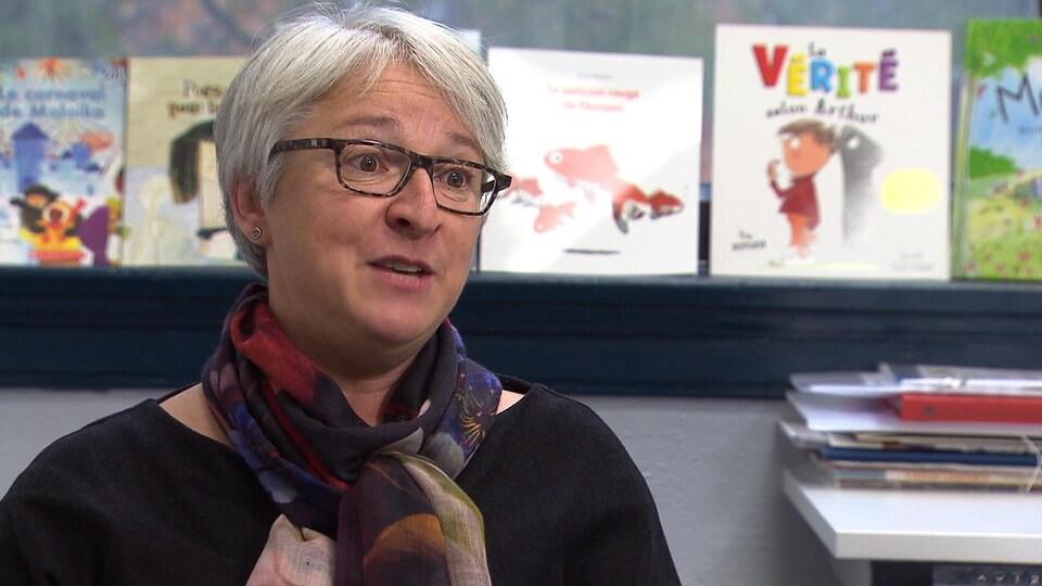 Une femme avec des lunettes et un foulard assise devant une rangée de livres pour enfants.