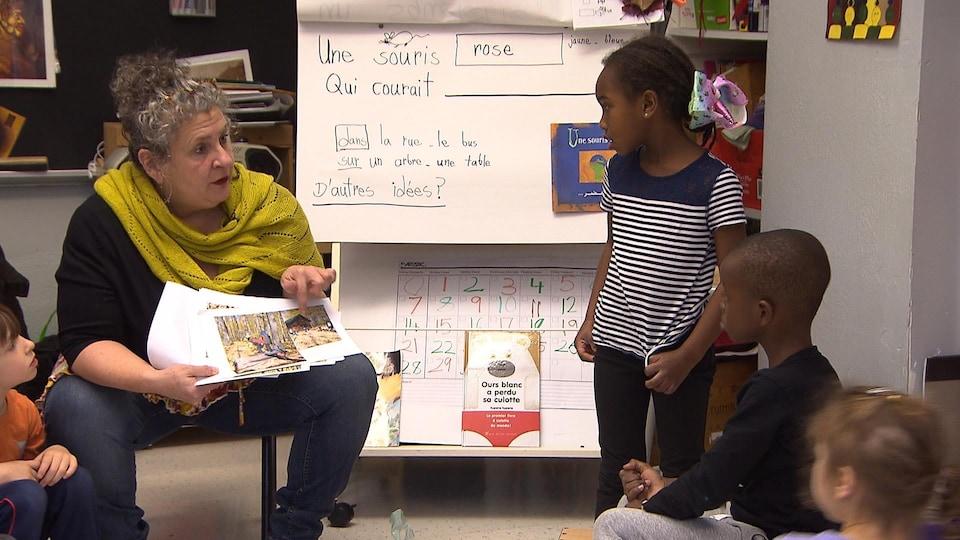 Une enseignante lit un livre à plusieurs enfants attentifs.