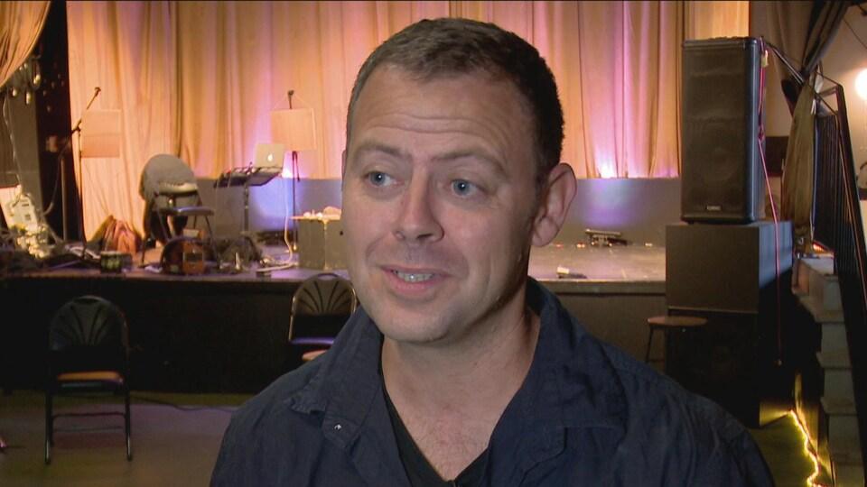 Mathieu Bec répond aux questions d'une journaliste dans une salle de spectacles.