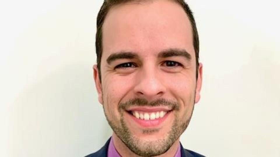 Un homme en veston et cravate qui sourit