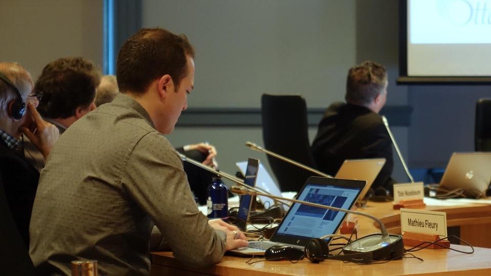 Le conseiller est assis à une table devant un ordinateur qu'il consulte pendant la réunion du comité