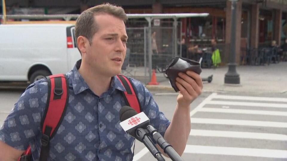 Un homme brandit un masque, alors qu'il accorde une entrevue à la caméra