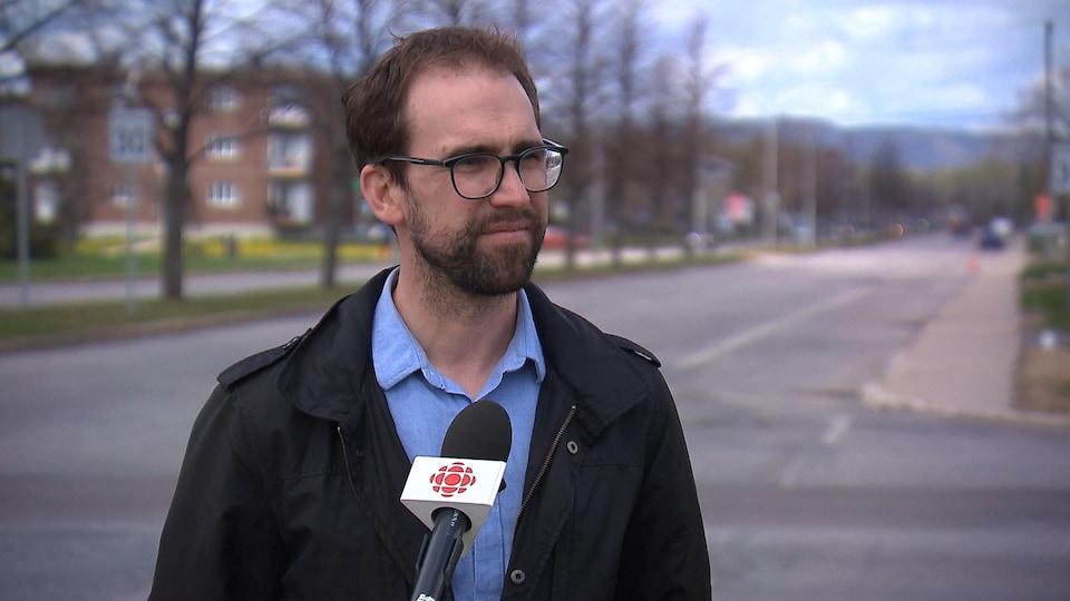 Mathieu Pineault est dans une rue de Baie-Comeau et parle au micro de Radio-Canada.