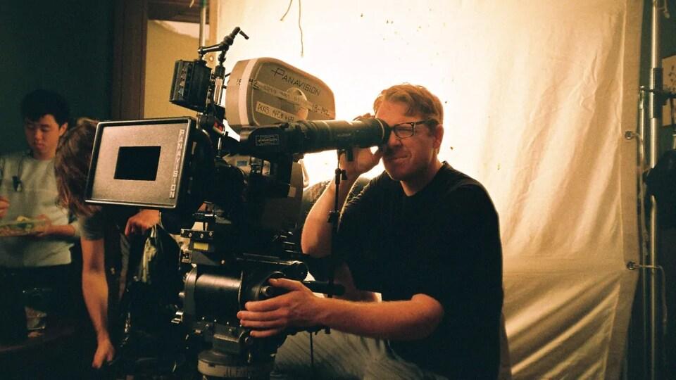 Un homme derrière une caméra sur un plateau de tournage.