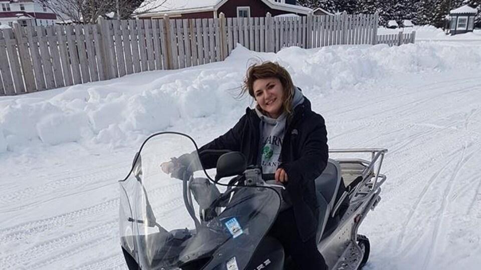 La jeune femme est souriante au volant de sa motoneige.