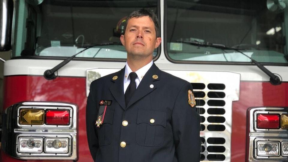 Matt Covey en uniforme devant un camion de pompiers.
