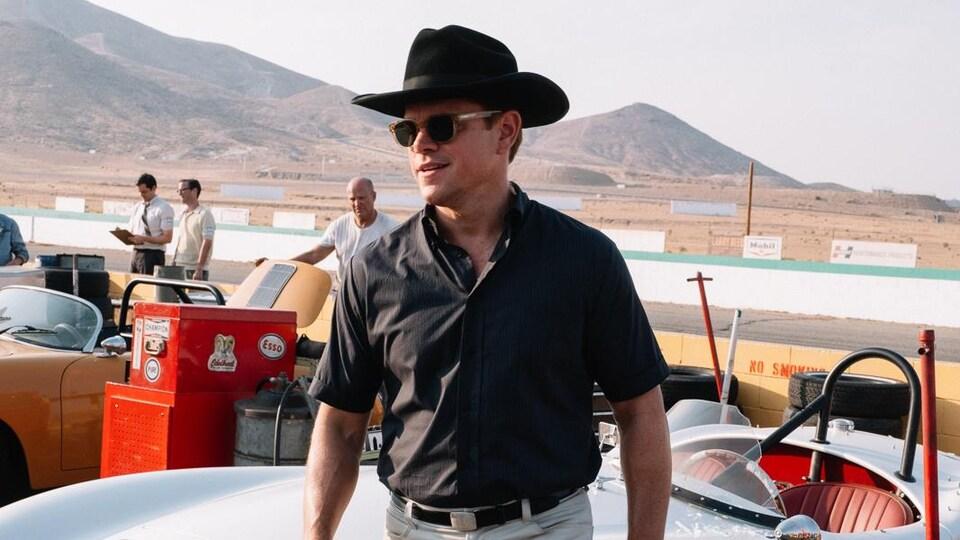 Un homme portant un chapeau de cowboy affiche un sourire près d'une voiture sur une piste de course en plein milieu du désert.