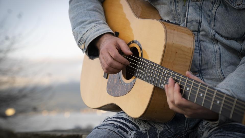 Gros plan sur les mains de Matt Stern qui joue de la guitare.