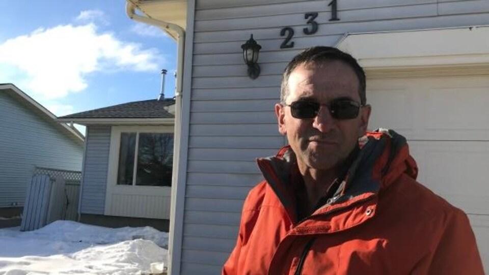 Matthew Doherty, debout à l'extérieur devant sa résidence