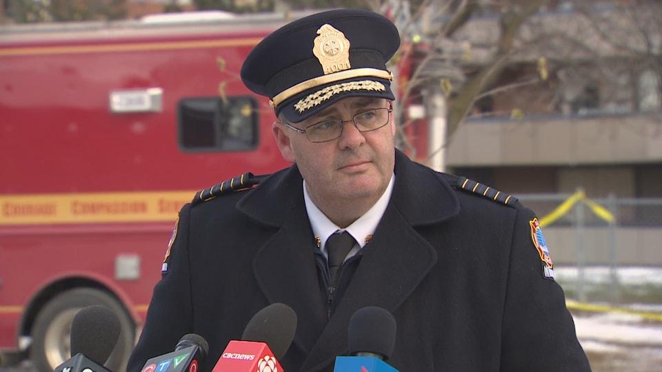 Le chef des pompiers de Toronto s'adresse aux médias dans la rue devant un camion rouge.