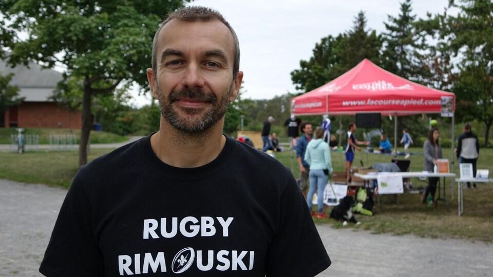 Un homme porte un t-shirt à l'effigie de son club de rugby de Rimouski.