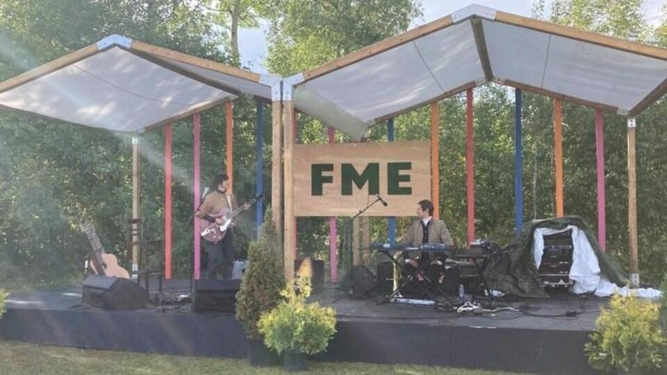 La chanteuse est en prestation à l'extérieur avec un autre musicien.