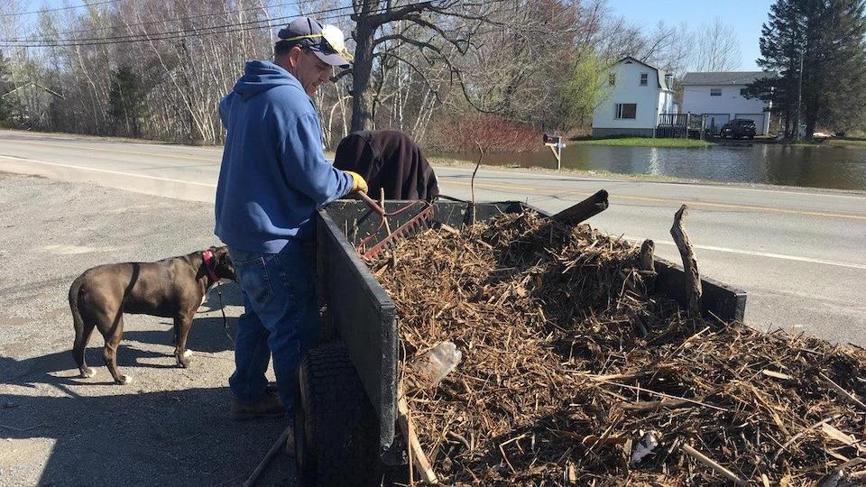 Un homme vide au bord de la route une charrette chargée de débris de bois et de végétation