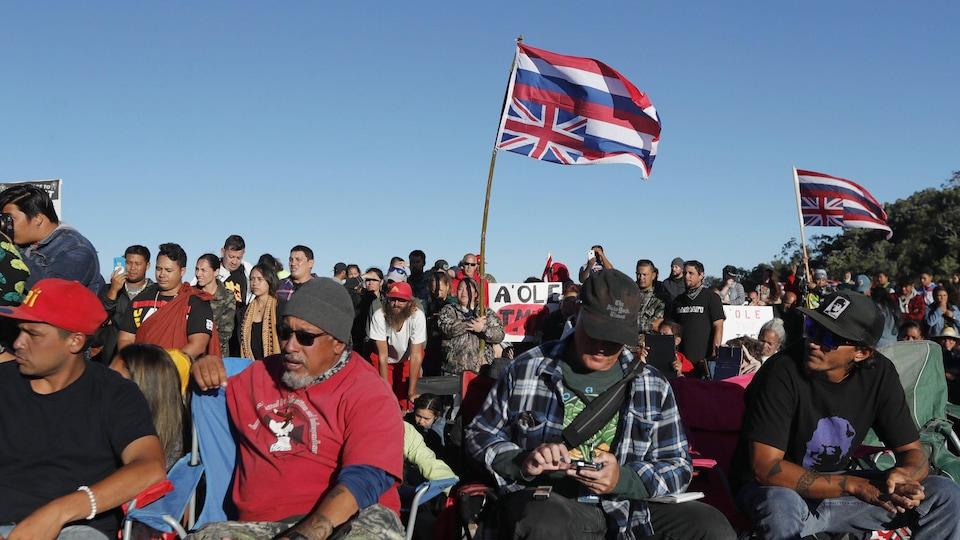 Plusieurs personnes sont assises et tiennent des drapeaux hawaïens.