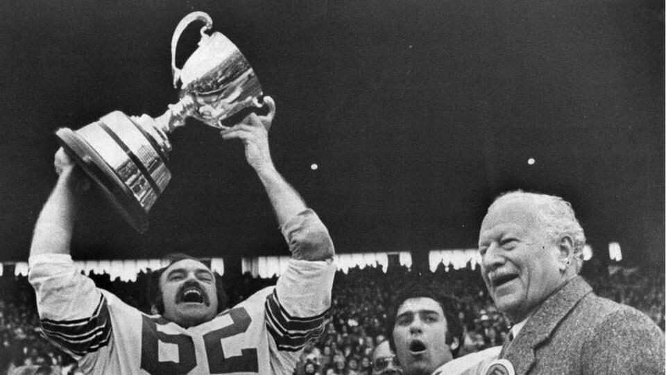Un joueur de football soulève une coupe en signe de victoire dans une photo en noir et blanc.