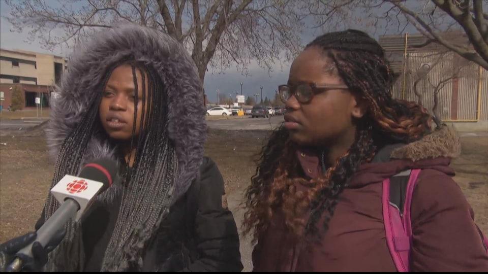 Les jeunes filles sont interviewées à l'extérieur de l'école sur le trottoir.