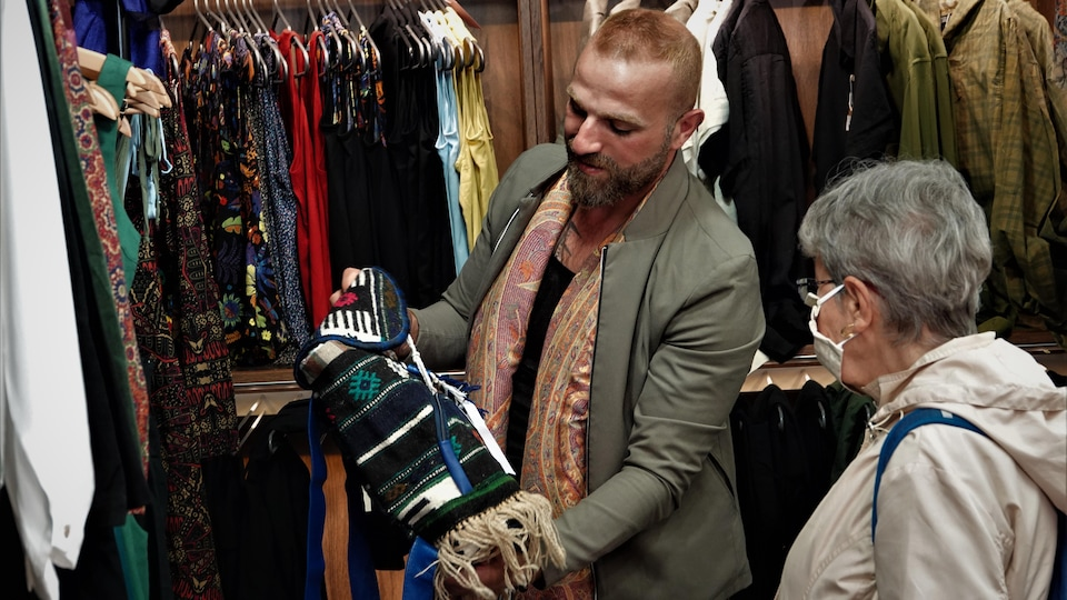 L'un des directeurs du magasin montre un sac à une cliente.