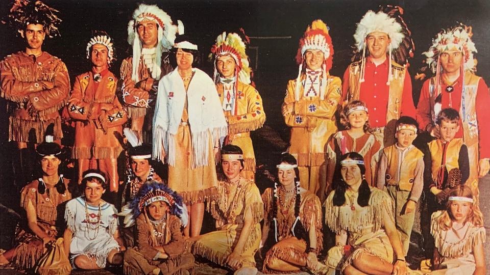 Il est accompagné des membres d'une troupe de danse wendat. Ils portent tous leur habit traditionnel.