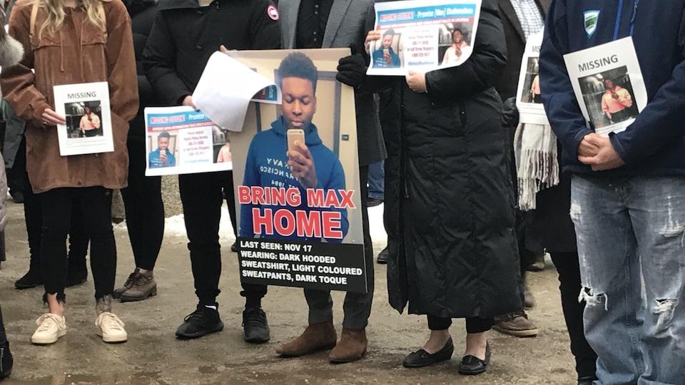Des gens tiennent des photos et posters de Max, porté disparu le 17 novembre à Regina.