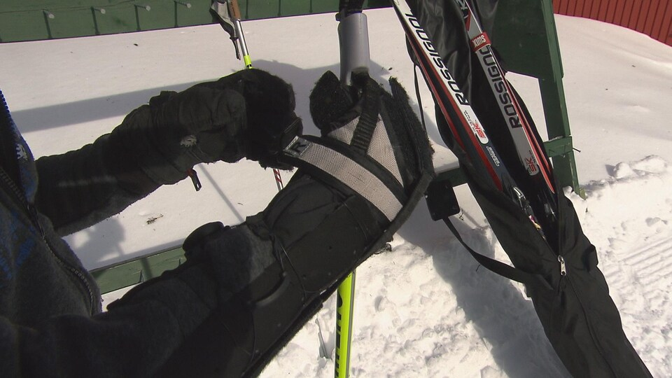 Maxence installe la prothèse qui lui permet de tenir son bâton de ski.